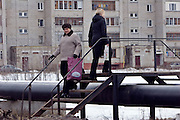 Beloozersky, Russia, 11/03/2007.<br /> Residents clamber over overground pipes that are part of the dilapidated centralised heating system which serves the apartments behind.