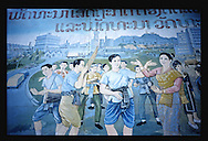 communist Propaganda, Vientiane, Laos, Asia. Ethnic characters are dancing and playing music. High cultural contrast and shock with industrial area paint in background.