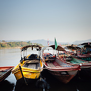 Long tail boats tied up on Mekhong River at Chiang Kong, Thailand