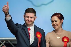 © Licensed to London News Pictures . 04/12/2015 . Oldham , UK . Labour candidate JIM MCMAHON gives a thumbs up , as his wife CHARLENE stands beside him as he is declared the victor at the count at the Oldham West and Royton by-election , at the Queen Elizabeth Hall in Oldham . The by-election was called following the death of MP Michael Meacher . Photo credit : Joel Goodman/LNP