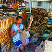A worker shaping the wood in the Allegre Guitar factory in Mactan, where guitar making by hand is made famous.