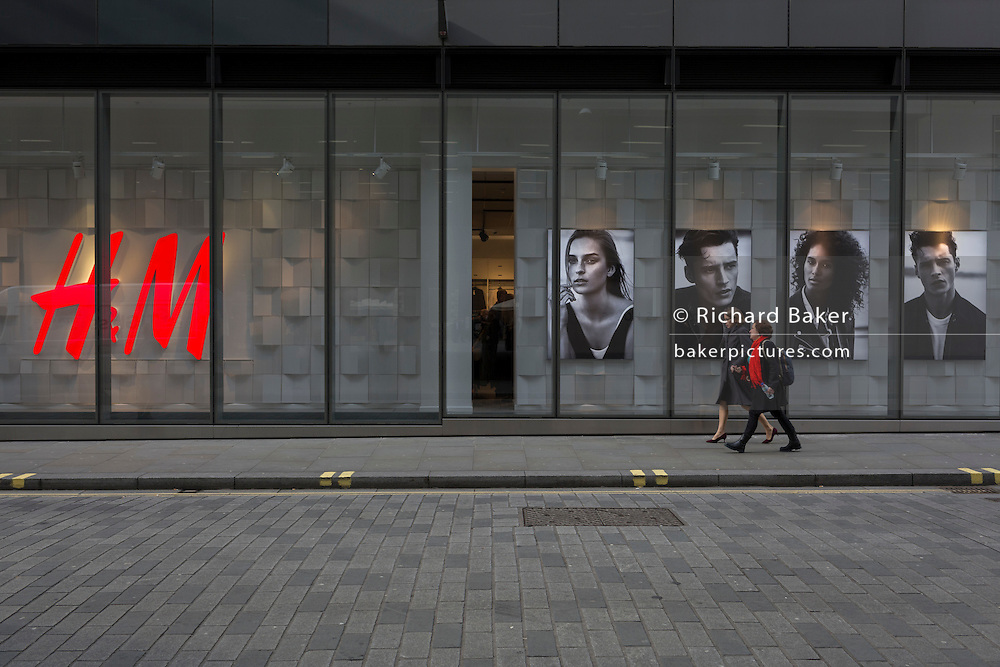 Passers-by walk along the street, outside an H&M retail shop, on 16th February 2017, in the City of London, England.