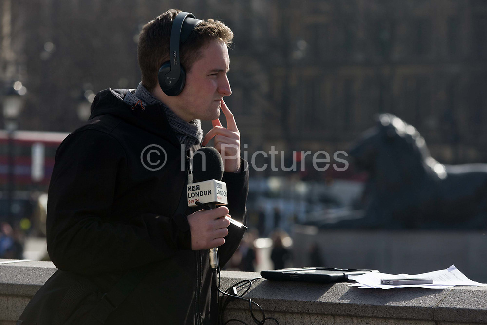 A BBC London 94.9 radio reporter, on location in Trafalgar Square after the unveiling of the Fourth Plinth artwork. The journalist looks into the distance, thinking about the report he is soon to make live on air during the current news item - the unveiling of the most recent artwork on the Fourth Plinth by German artist Hans Haacke. Holding the microphone and with other broadcast equipment resting on a ledge, he considers how best to describe the scene for London's radio audience. RAJAR data, the audience measurement system in the UK, showed that BBC London 94.9 audience reach for the second quarter in 2014 was 572,000.