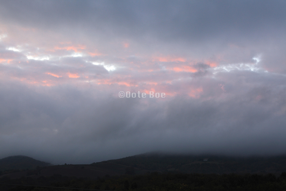 wind swept clouds with silhouetted hilly landscape