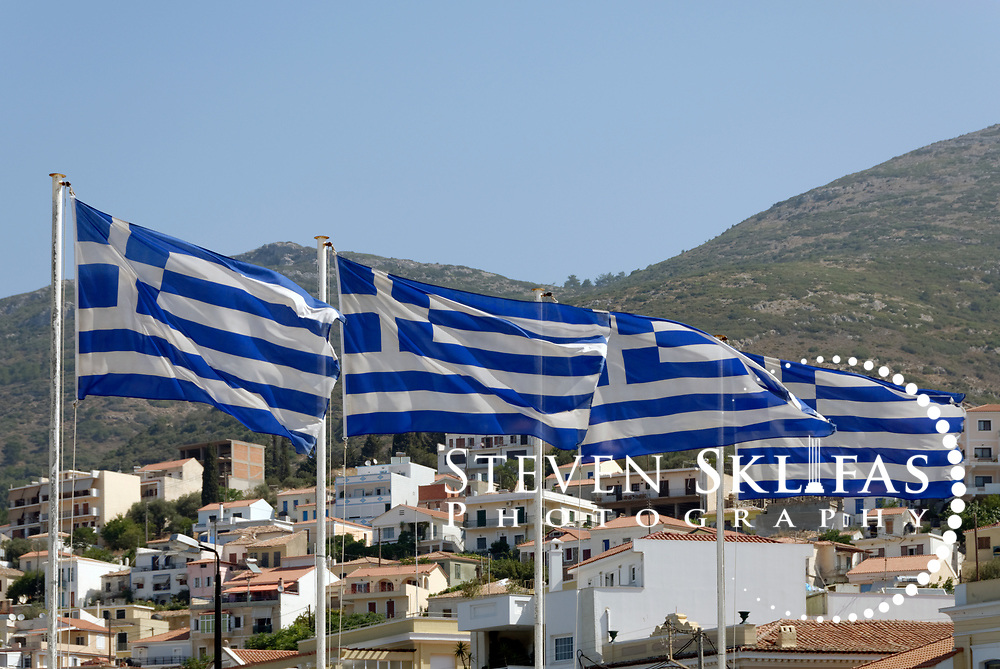 Samos. Greece. View of four flags of Greece flying proudly on the waterfront of Vathy or Samos town. Vathy is situated on a horseshoe shaped bay and is the capital and largest town of Samos.