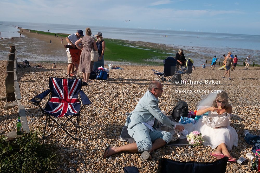Newlywed groom Paul and bride Zoe have just been married at a nearby beach venue and continue their wedding ceremony by eating bags of chips on the shingle overlooking the Thames Estuary at Whitstable,  on 18th July 2020, in Whitstable, Kent, England. Due to the Coronavirus pandemic restrictions, large social gatherings such as weddings are currently restricted to a maximum of 30 guests and officlas so Paul and Zoe's own ceremony was witnessed by just a few family and friends.