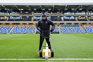 AFC Wimbledon member of staff painting the lines with main stand of Plough Lane behind during the EFL Sky Bet League 1 match between AFC Wimbledon and Sunderland at Plough Lane, London, United Kingdom on 16 January 2021.