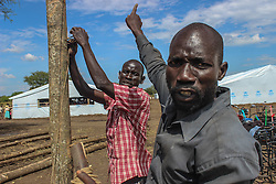 Local Ugandans are hired to build the new reception centre at BidiBidi. They say they are happy to welcome refugees. In addition, there has been a rise of jobs in the area. More than 300,000 South Sudanese refugees have fled from the country's civil war into Uganda since fighting broke out in July. They mostly travel by foot for days through the bush as roads have been blocked or are too dangerous to cross. The massive influx of refugees has caused a strain in humanitarian aid due to large numbers and lack of funding. BidiBidi settlement is now the third largest in the world and holds more than 210,000 people since its opening in September.
