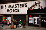 The shell of the empty HMV record store, 'home of entertainment since 1921',  with the famous 'His Master's Voice' sign, looks sadly down at the masked people shopping until the last moment before the second national coronavirus lockdown on 4th November 2020 in London, United Kingdom. The fly posters lashing out at both the Tories and Tesco's add a dose of surreal irony largely missed by the shoppers.  Radical measures will be needed to persuade shoppers to return in large numbers after December 2 when lockdown ends. The new national lockdown is a huge blow to the economy and for individuals who were already struggling, as Covid-19 restrictions are put in place until 2nd December across England, with all non-essential businesses closed.