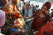 Pilgrims performing ceremonies on the banks of the Shipra River while bating during Kumbh Mela festival, Ujjain, Madhya Pradesh, India. The Kumbh Mela festival is a sacred Hindu pilgrimage held 4 times every 12 years, cycling between the cities of Allahabad, Nasik, Ujjain and Hardiwar.  Participants of the Mela gather to cleanse themselves spiritually by bathing in the waters of India's sacred rivers. Kumbh Mela is one of the largest religious festivals on earth, attracting millions from all over India and the world. Past Melas have attracted up to 70 million visitors.
