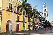 The Cathedral of Veracruz towers above the palm trees lining the Plaza de las Armas and the Portales de Veracruz in the historic center of the city of Veracruz, Mexico. The area is the main public square in Veracruz.