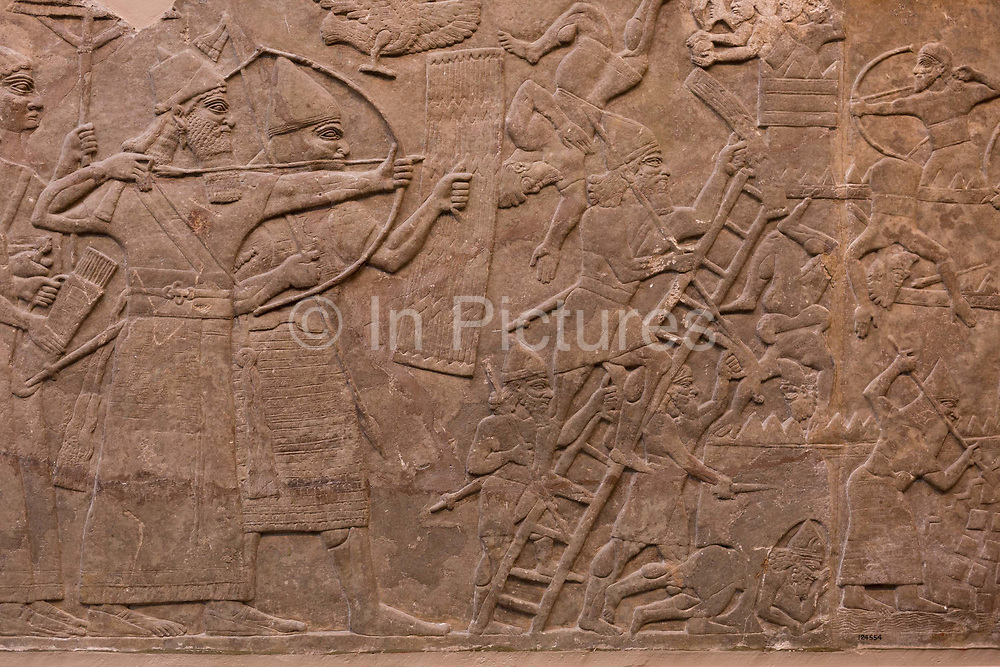 A detail from an ancient Assyrian stone carving 865-860BCdepicting an attack on an enemy town by a river, in the British Museum, on 11th April 2018, in London, England.