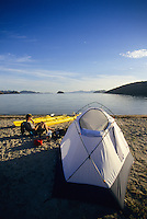 A young man rests at camp while sea kayaking in Bahia Conception, Sea of Cortez, Mexico.