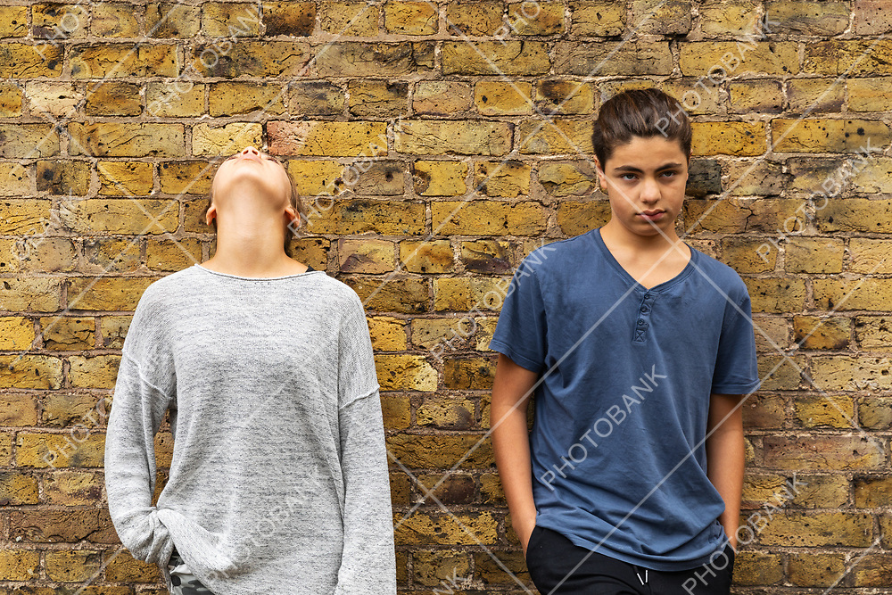 Two depressed young teens stand in front of a brick wall. Front view. Nobody inside