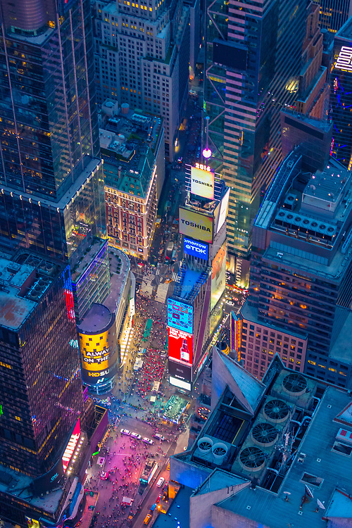 """Aerial photograph (helicopter). Times Square is a major commercial intersection and neighborhood in Midtown Manhattan, New York City, at the junction of Broadway and Seventh Avenue, and stretching from West 42nd to West 47th Streets. Brightly adorned with billboards and advertisements, Times Square is sometimes referred to as The Crossroads of the World, The Center of the Universe, the heart of The Great White Way, and the """"heart of the world"""". One of the world's busiest pedestrian intersections, it is also the hub of the Broadway Theater District and a major center of the world's entertainment industry. Times Square is one of the world's most visited tourist attractions, drawing an estimated 50 million visitors annually. Approximately 330,000 people pass through Times Square daily, many of them tourists, while over 460,000 pedestrians walk through Times Square on its busiest days."""