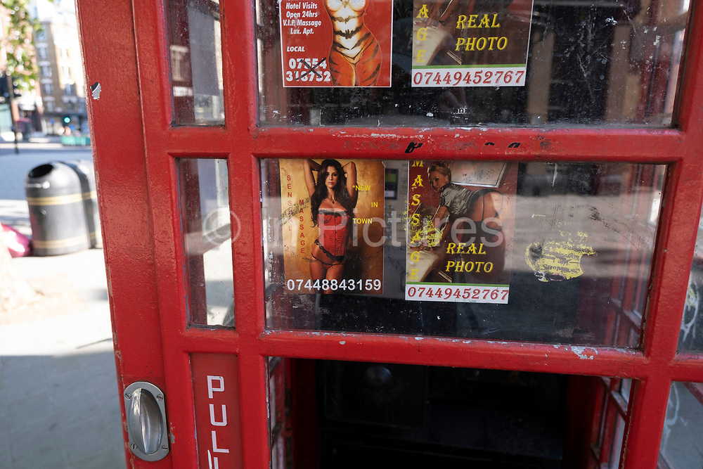 Public telephone box which has sex cards tacked up inside on 25th June 2020 in London, United Kingdom. These advertising cards for prostitutes are how people advertise for sexual services under the guise of other services like massage for example.