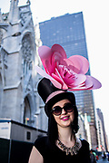 New York, NY - April 16, 2017. A woman sports a top hat with a large decorative blossom at New York's annual Easter Bonnet Parade and Festival on Fifth Avenue.