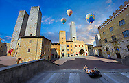 Hot Air Balloons over the Piazza Duomo (Cathedral Square) of San Gimignano with its medieval towers built as defensive towers and also to show the families wealth by the height of the tower. A UNESCO World Heritage Site. San Gimignano; Tuscany Italy .<br /> <br /> Visit our ITALY PHOTO COLLECTION for more   photos of Italy to download or buy as prints https://funkystock.photoshelter.com/gallery-collection/2b-Pictures-Images-of-Italy-Photos-of-Italian-Historic-Landmark-Sites/C0000qxA2zGFjd_k<br /> If you prefer to buy from our ALAMY PHOTO LIBRARY  Collection visit : https://www.alamy.com/portfolio/paul-williams-funkystock/sangimignano.html