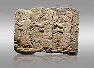 Picture & image of Hittite monumental relief sculpted orthostat stone panel of a Procession Limestone, Karkamıs, (Kargamıs), Carchemish (Karkemish), 900-700 B.C. Anatolian Civilisations Museum, Ankara, Turkey.<br /> <br /> It is a depiction of three marching female figures in long dress with a high headdress at their head. These women are considered to be the nuns of the Goddess Kubaba. The figures in the front and behind have a round mirror in their right hand while the figure in the middle has a bunch of spica in her right hand. Figures carry objects similar to a sceptre in their left hand.  <br /> <br /> Against a gray background. .<br />  <br /> If you prefer to buy from our ALAMY STOCK LIBRARY page at https://www.alamy.com/portfolio/paul-williams-funkystock/hittite-art-antiquities.html  - Type  Karkamıs in LOWER SEARCH WITHIN GALLERY box. Refine search by adding background colour, place, museum etc.<br /> <br /> Visit our HITTITE PHOTO COLLECTIONS for more photos to download or buy as wall art prints https://funkystock.photoshelter.com/gallery-collection/The-Hittites-Art-Artefacts-Antiquities-Historic-Sites-Pictures-Images-of/C0000NUBSMhSc3Oo