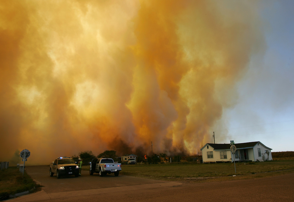 Alton, TX - 19 Jan 2009 - .A wall of smoke blows down Everest St. north of Alton on Monday afternoon as flames from a rapidly moving fire approach the area..Photo by Alex Jones / ajones@themonitor.com