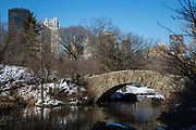 The beautiful, schist Gapstow Bridge over northeast end of The Pond, Central Park, Manhattan, New York City, New York, United States of America.  The bridge is famous for offering one of the best views of the city skyline. Central Park is covered in snow.