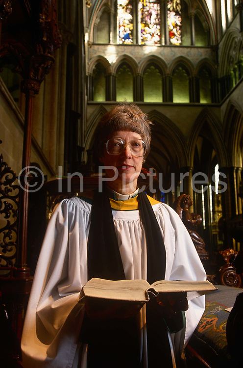 """A portrait of Britain's first lady deacon, Christine Farrington at Salisbury Cathedral. Standing in the grand architecture of the nave. Deacon is a ministry in the Christian Church that is generally associated with service of some kind, but which varies among theological and denominational traditions. In many traditions the """"diaconate"""", the term for a deacon's office, is a clerical office; in others it is for laity. The word """"deacon"""" is derived from the Greek word diakonos, standard ancient Greek for """"servant"""", """"waiting-man"""", """"minister"""" or """"messenger"""". Salisbury Cathedral, formally known as the Cathedral Church of the Blessed Virgin Mary, is an Anglican cathedral in Salisbury, England, and is considered one of the leading examples of Early English architecture. The main body was completed in only 38 years, from 1220 to 1258."""