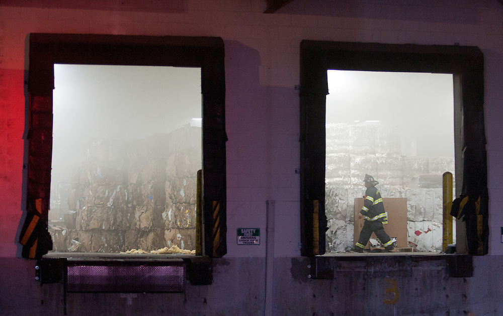 Mansfield, MA 09/13/2011.A firefighter walks through the smoky interior of Miller Recycling during Tuesday night's 4 alarm fire..Wicked Local Photo by Alex Jones