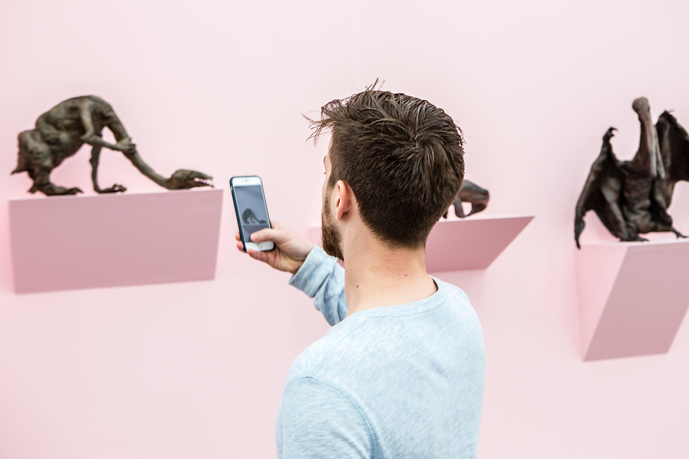 """New York, NY - 5 May 2017. The opening day of the Frieze Art Fair, showcasing modern and contemporary art presented by galleries from around the world, on Randall's Island in New York City. A man takes a photo of Francis Upritchard's bronze """"Strangle,"""" 2015, in the Anton Kern Gallery."""