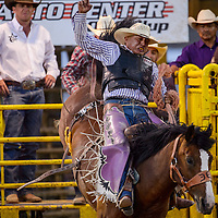 Saddle bronc rider Vince Tsosie holds tight as his horse springs from the chute during the first round of the Fourth of July PRCA rodeo Saturday in Window Rock.