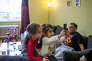 """Father Eduard Polanski (47) in the back with his daughters Sara (6) on the left and Kristina (4) taking a photograph in their temporary home in Ostrava. Sara's mother was advised from one of the schools that she should not enrol her daughter there - after the girl passed the enrolment test - because Sara is so """"slim"""". Mother Ingrid Kandracova (36) new that the final decision is on her side and she refused the advice and enrolled her daughter in the school."""