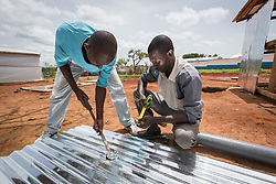 4 June 2019, Meiganga, Cameroon: CAR refugee Moussa Inoussa (left) and Dengui Amadou (right) make the hole for a ventilation pipe in a steel plate to be mounted as roof of a latrine in the Ngam refugee camp. Supported by the Lutheran World Federation, the Ngam refugee camp, located in the Meiganga municipality, Adamaoua region of Cameroon, hosts 7,228 refugees from the Central African Republic, across 2,088 households.