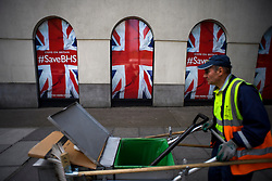 """© Licensed to London News Pictures. 10/06/2016. London, UK. A road sweeper walks past Signs reading """"COME ON BRITAIN #Save BHS in the window of British Homes Stores (BHS) Headquarters in central London. British department store BHS is due to be liquidated after a buyer for the company failed to materialise. Photo credit: Ben Cawthra/LNP"""