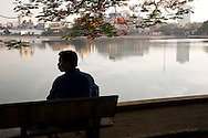 A Vietnamese man sitting on a bench along Giang Vo lake obserses something off to the side, Hanoi, Vietnam, Southeast Asia