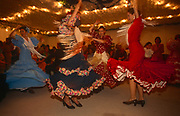 Spanish ladies dance Flamenco into the night at a private party in a marquee called a Caseta during the annual Feria de Abril, on 11th June 1999, in Seville, Andalucia, Spain. Rows of temporary marquee tents, or casetas, host families, corporations and friends into the late hours during the April Fair which begins begins two weeks after the Semana Santa, or Easter Holy Week in the Andalusian capital.