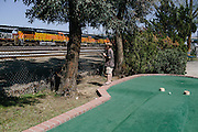 Connor Ricket, 6, looks out at the trainyard while playing miniature golf at an small amusement park in Bakersfield. The park is nestled snuggly next to the yard that moves oil and coal in and out of the area.