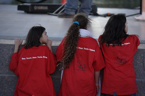 Stock photo of three young girls at the park's performance stage watching preparation for the show