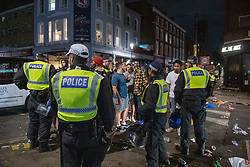© Licensed to London News Pictures. 19/07/2020. London, UK. Metropolitan police officers look on as collegues engage with the crowd. A crowd has been dispersed by police from Kingsington Park Road in Notting Hill. The crowd was ordered to leave the area under a Section 35 order. The Crowd were generally compliant and left the area peacefully. Photo credit: Peter Manning/LNP