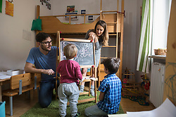 Little boy is writing on a blackboard, parents and the older brother are watching, Munich, Germany
