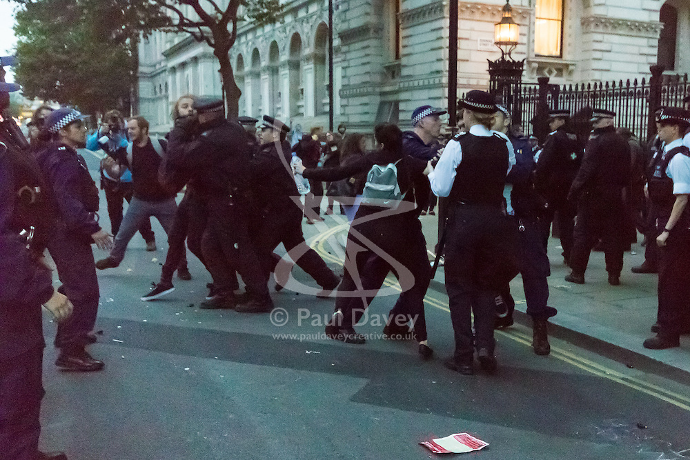 London, May 27th 2015. A scuffle breaks out as protesters demonstrate outside Downing street against the Tories' ongoing campaign of austerity on the day the Queen delivered her speech to Parliament