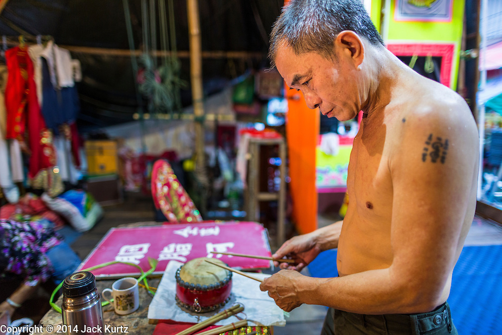 """19 AUGUST 2014 - BANGKOK, THAILAND:  A percussionist with the Lehigh Leng Kaitoung Opera troupe checks a small drum before a performance at Chaomae Thapthim Shrine, a small Chinese shrine in a working class neighborhood of Bangkok. The performance was for Ghost Month. Chinese opera was once very popular in Thailand, where it is called """"Ngiew."""" It is usually performed in the Teochew language. Millions of Chinese emigrated to Thailand (then Siam) in the 18th and 19th centuries and brought their culture with them. Recently the popularity of ngiew has faded as people turn to performances of opera on DVD or movies. There are still as many 30 Chinese opera troupes left in Bangkok and its environs. They are especially busy during Chinese New Year and Chinese holiday when they travel from Chinese temple to Chinese temple performing on stages they put up in streets near the temple, sometimes sleeping on hammocks they sling under their stage. Most of the Chinese operas from Bangkok travel to Malaysia for Ghost Month, leaving just a few to perform in Bangkok.        PHOTO BY JACK KURTZ"""