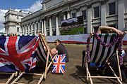 Watching live TV coverage of Equestrian events, British spectators and other sports fans sit in summer deckchairs at the old Royal Naval College, Greenwich on day 4 of the London 2012 Olympic Games. Greenwich Park is hosting the Olympic Equestrian competitions, plus the combined running and shooting event of the Modern Pentathlon. The Old Royal Naval College is the architectural centrepiece of Maritime Greenwich, a World Heritage Site in Greenwich, London. The buildings were originally constructed to serve as the Royal Hospital for Seamen at Greenwich, now generally known as Greenwich Hospital, which was designed by Christopher Wren, and built between 1696 and 1712.