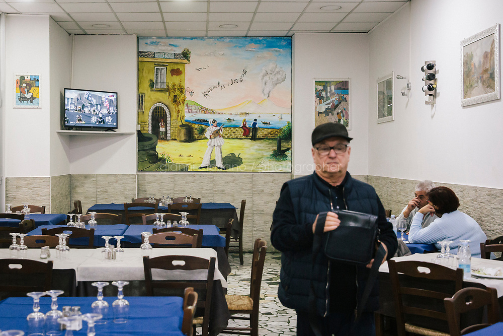 """NAPLES, ITALY - 7 NOVEMBER 2019: Customers are seen here at the Trattoria Avellinese, a family-run restaurant in Naples, Italy, on November 7th 2019.<br /> <br /> Peppino is the typical restaurant of the Neapolitan residents living  around the central station of Naples. Avellinese is not a surname; it was the nickname of Peppino (Giuseppe) Cipriano. He was called Avellinese because he came from Avellino, a city in the interior of the region. When Peppino he arrived in Naples in 1928, his inspired his Neapolitan trattoria to the characteristics of Avellino cuisine. """"The will to propose the simple things of gastronomy was the inspiring principle of our father; and we, after almost a hundred years from the foundation, continue to keep the trattoria's mission intact"""", says Carmela, the daughter of Peppino, one of the three brothers who runs the restaurant.<br /> Since the 1980s his three children - Salvatore (56), Carmela (55), and Tina (52) - keep the restaurant open every day of the week."""