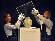 """© Licensed to London News Pictures. 28/09/2012. London, UK Auction room staff replace a protective box around A highly important Fatimid white-ground lustre pottery jar from Egypt dated 10th/11th century. The jar is expected to fetch 300,000-500,000GBP. Sotheby's Auction rooms in New Bond Street, London hold a photo call for their upcoming """"arts of the Islamic World"""" auction which is expected to realise in the region of 5 million GBP . Photo credit : Stephen Simpson/LNP"""