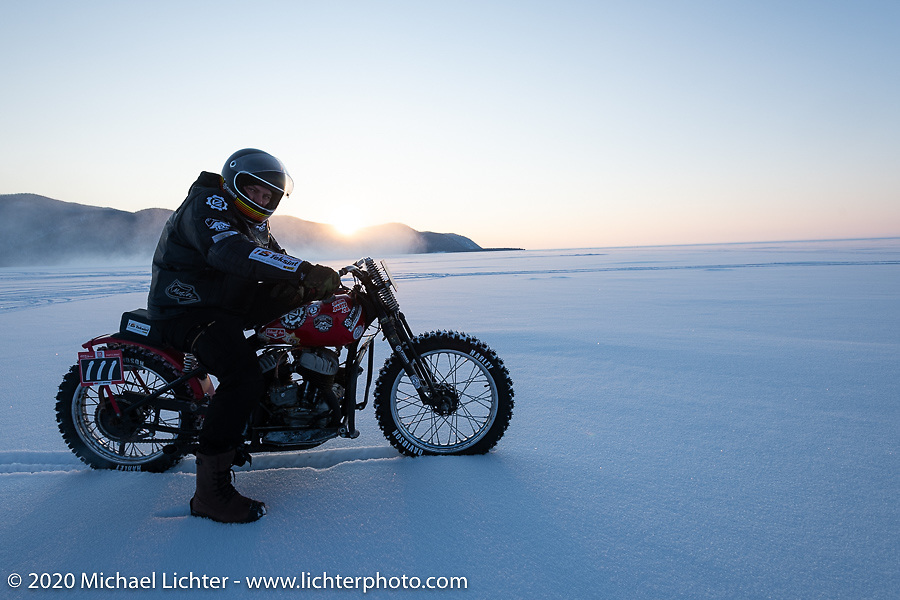 """Victor Dokuchaev on his 1942 WR 45"""" Harley-Davidson Flathead racer checks out the setting sun from the middle of Lake Baikal during the Baikal Mile Ice Speed Festival. Maksimiha, Siberia, Russia. Friday, February 28, 2020. Photography ©2020 Michael Lichter."""