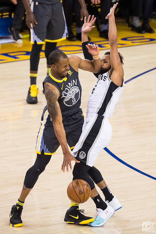 Golden State Warriors forward Andre Iguodala (9) hits San Antonio Spurs guard Patty Mills (8) in the face during Game 2 of the Western Conference Quarterfinals at Oracle Arena in Oakland, Calif., on April 16, 2018. (Stan Olszewski/Special to S.F. Examiner)