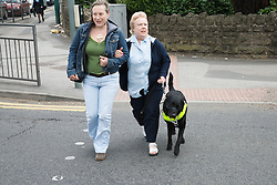 Visually impaired woman crossing the road with her friend and guide dog,