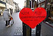 Nederland, Nijmegen, 17-03-2020  In de binnenstad hebben jongeren hartjes opgehangen . Ze doen dit om mensen in de zorg die onderweg zijn naar hun werk een hart onder de riem te steken . Foto: Flip Franssen.