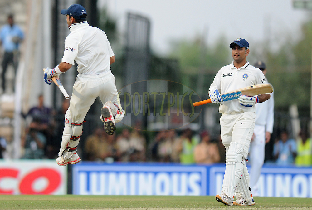 MS Dhoni captain of India looks on as teammate Virat Kohli of India celebrates after scoring a century during day three of the 4th Airtel Test Match between India and England held at VCA ground in Nagpur on the 15th December 2012..Photo by  Pal Pillai/BCCI/SPORTZPICS .