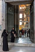 Muslim women at Hagia Sophia Ayasofya Muzesi mosque museum in niquab using smartphone to take photograph Istanbul, Turkey