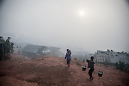Villagers collect water on a foggy morning in Chachuluong Village, Northern Laos